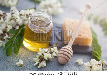 jar of acacia honey with a dipper and acacia flowers - food and drink