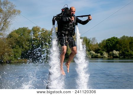 Thrillseeker, Athelete Strapped To Jet Lev, Levitation Hovers Over Lake With Blue Sky And Trees In B