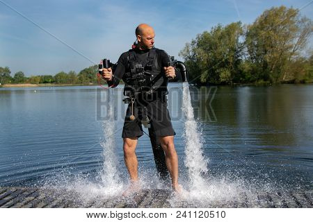 Thrillseeker, athelete strapped to Jet Lev, levitation hovers over lake with blue sky and trees in background. poster