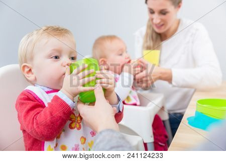 Portrait of a cute baby boy learning to drink water from a plastic glass, while sitting in a high chair next to another baby at home or in a modern daycare center for infants