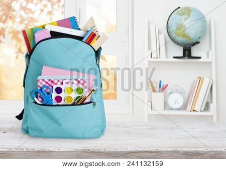 School Backpack On Wooden Table Over Children Room Interior Background