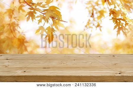 Wooden Table In Front Of Abstract Blurred Colorful Autumn Background