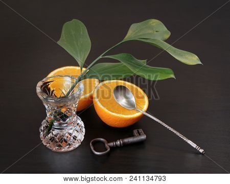 Two Halves Of Juicy Orange, Beautiful Vintage Spoon, Green Branch In Crystal Vase, Ancient Steel Key