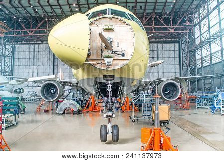 Passenger Airplane On Maintenance Of Engine And Fuselage Check Repair In Airport Hangar. With An Ope