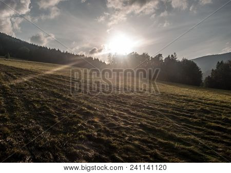 Evening Meadow With Shadows, Sunlight, Forest On The Background, Sun And Blue Sky With Clouds Near K