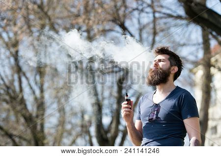 Bearded Man Smokes Vape On Sunny Day. Electronic Cigarette Concept. Man With Long Beard Looks Relaxe