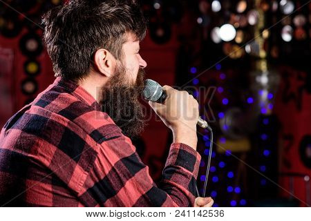 Man In Checkered Shirt Holds Microphone, Singing Song, Karaoke Club Background. Guy Likes To Sing In