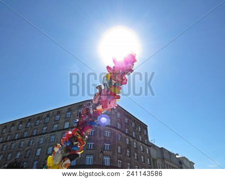 Pile Of Helium Filled Flying Balloons For Children With The Sky And Sun In Background, May 2018, War