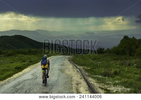 Man Travel Alone By Bicycle In Rainy Landscape. Traveler Cycle On Mountain Road Enjoying Beautiful M