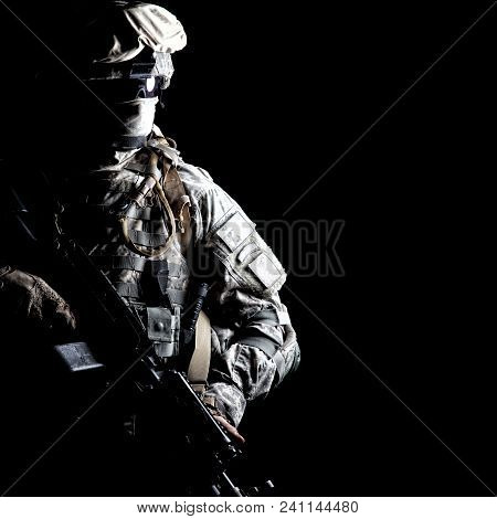 Armed Army Soldier In Camouflage Uniform, With Hidden Face, Sneaking In Dark During Combat, Counter