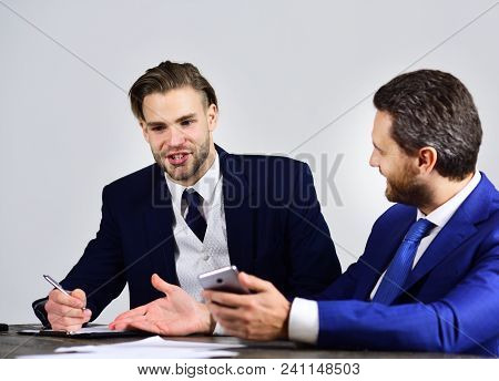 Friends With Happy Faces Discuss Startup And Surf Internet. Business People Hold Smartphone, Pen And