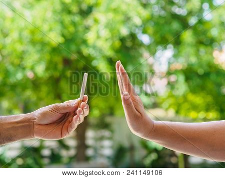No Smoking. Close Up Of Male Hands Holding Cigarettes And Proposing It To Person. The Human Arm Is G