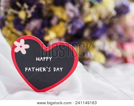 Happy Father's Day Concept. Wooden Tag With Happy Father's Day Text And Two Red Heart On Dry Flower