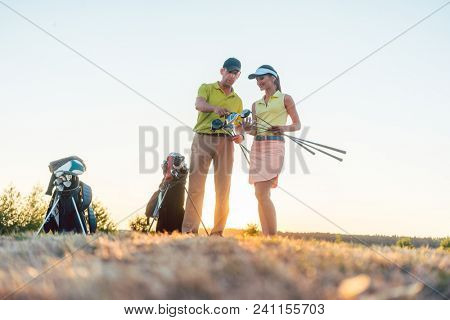 Low-angle view of a skilled golf instructor teaching a young woman how to use different professional golf clubs during class outdoors at sunset