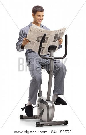 Young man in pajamas reading a newspaper on a stationary bike isolated on white background