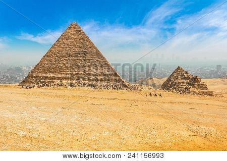 The Egyptian Pyramids Of Giza On The Background Of Cairo. Miracle Of Light. Architectural Monument.
