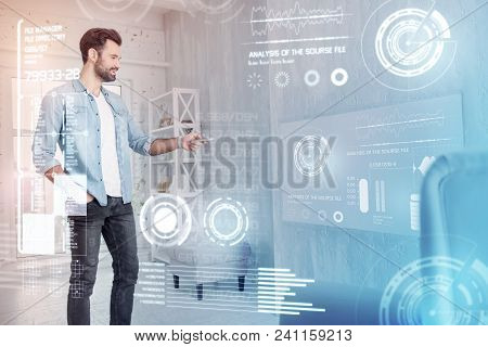 Nice System. Cheerful Young Man Smiling And Feeling Glad While Using His Remote Control At Home
