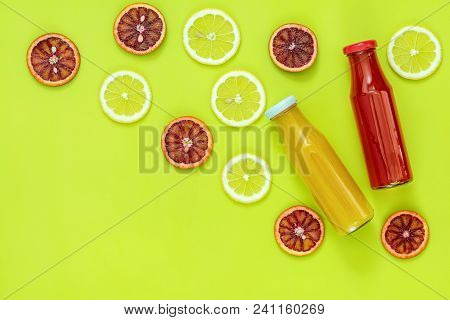 Beautiful Food Art Background. Yellow And Red Juice In Glass Bottles Sliced Lemon And Blood Orange F
