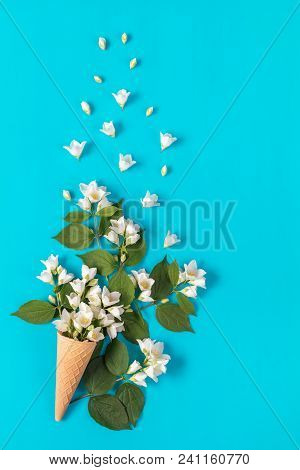 Waffle Cone With Jasmine Flower Bouquet On Blue Background. Flat Lay, Top View Floral Background.