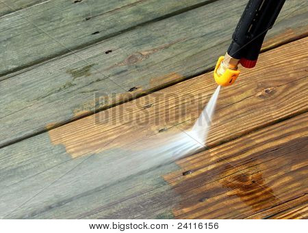 A pressure washer cleaning a wood deck poster