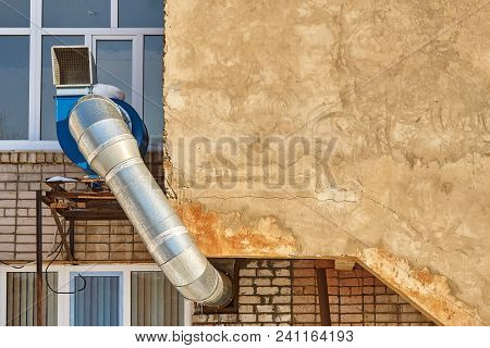 Exhaust System Protruding From A Brick Wall