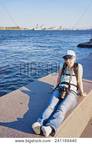 Young Girl With Digital Camera Sitting At The Embankment Of The Delaware River In Philadelphia, Penn