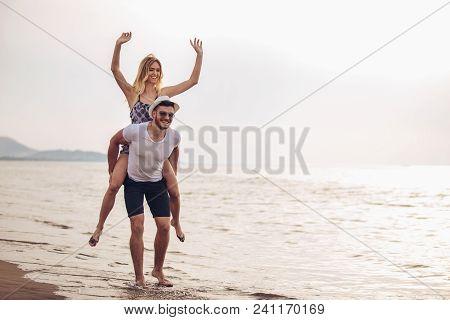 Happy Couple In Love On Beach Summer Vacations. Joyful Girl Piggybacking On Young Boyfriend Having F