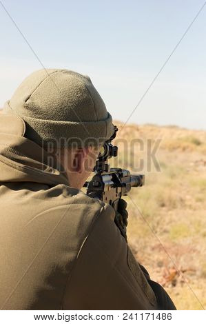 Shooting Man. Man In Camouflage With Gun Aiming.