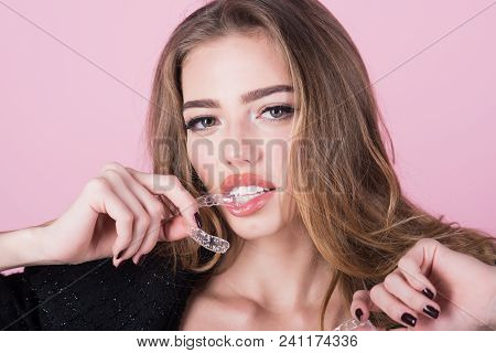 Close Up Of Plastic Transparent Brace In Hand Of Positive Young Woman. Woman Wearing Orthodontic Sil