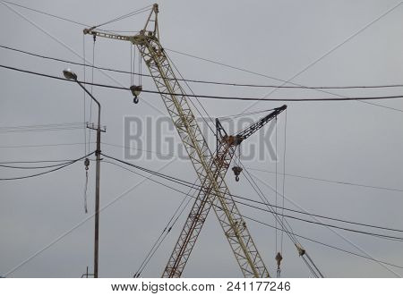 Construction Cranes And A Lamppost On A Gray Sky Background. Grunge Urban Background. Gray Sky