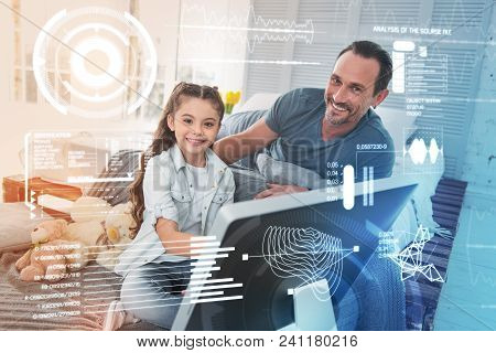 Looking Happy. Cheerful Emotional Girl Sitting In Front Of A Modern Device And Her Kind Father Smili
