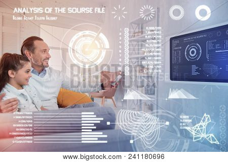 Testing System. Cheerful Young Man Holding A Remote Control While Sitting With His Positive Daughter