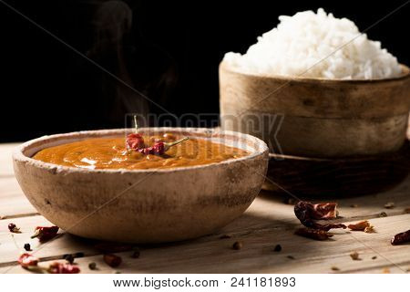 closeup of a bowl with a chicken korma curry and a bowl with cooked rice on an off-white wooden table