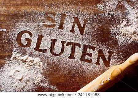 high-angle shot of a wooden table sprinkled with a gluten free flour where you can read the text sin gluten, gluten free written in spanish, next to a rolling pin