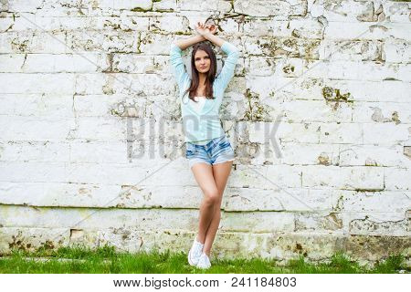 Young beautiful brunette woman in short blue jeans shorts posing against a stone wall background