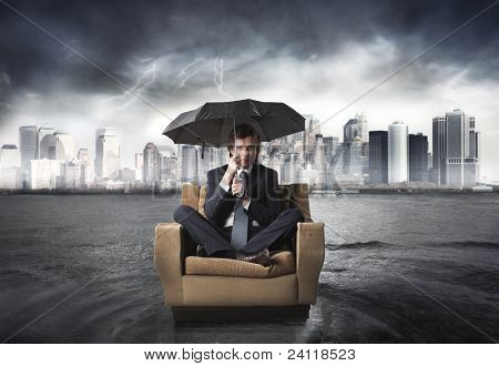 Businessman sitting under an umbrella on an armchair with cityscape in the background