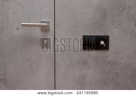 Light Switch On The Gray Textured Wall Next To The Door With Metallic Handle. Wall Temperature Regul