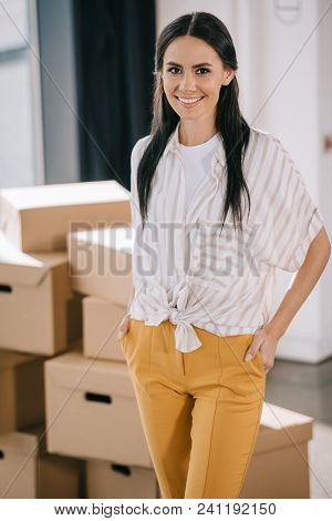 Woman Standing With Hands In Pockets And Smiling At Camera While Relocating In New Office