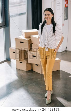 Happy Young Businesswoman Standing With Hands In Pockets And Smiling At Camera While Relocating In N