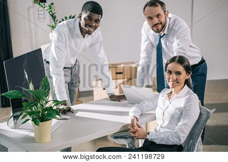 happy multiracial coworkers smiling at camera while relocating in new office poster