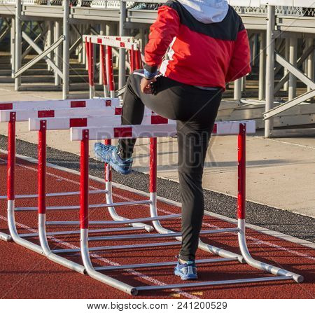 A High School Girl Track And Field Athlete Is Warming Up For Her Hurdle Race By Walking Over Hurdles