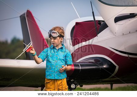 Boy Of The European Appearance In Yellow Shorts, A Blue Shirt With The Drawn Small Planes And In Avi