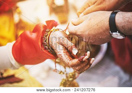 Men Ties The Holy Thread On The Wrist Of Indian Bride During Puja (pooja) Belief To Protect Her From