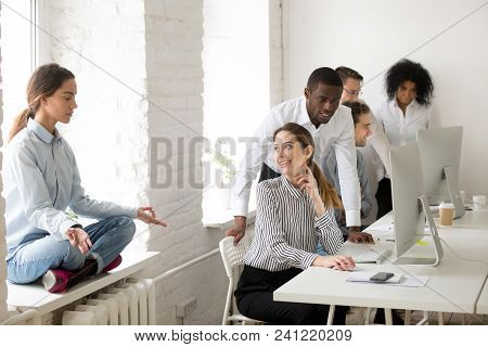 Young Woman Meditating Practicing Yoga Sitting At Office Sill Avoiding Colleagues Looking At Girl Wi