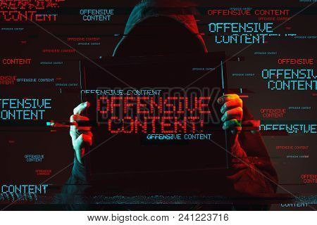Offensive Content Concept With Faceless Hooded Male Person Holding Computer Monitor, Low Key Red And