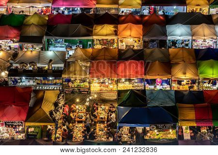 BANGKOK, THAILAND, MARCH 16, 2018 : Close shot on the colorful Rod Fai Ratchada night market with people having diner in Bangkok, Thailand