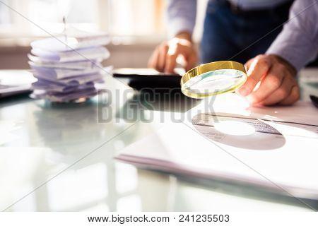 Businessperson's Hand Analyzing Bill