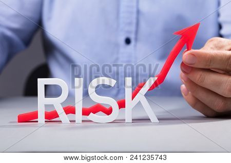 Businessperson Holding Red Increasing Arrow Behind The Risk Word Text On Table