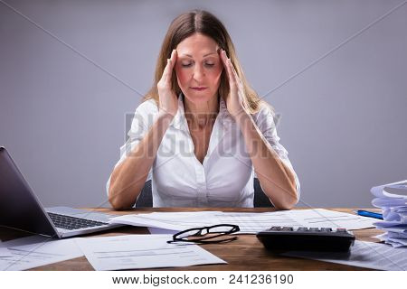Businesswoman Suffering From Headache Sitting In Office