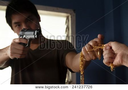 Gangster Or Thief Holding The Gun In Hand For Shoot Stealing Gold Necklace